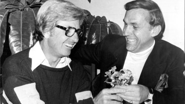 Let's be friends ... Bob Rogers and John Laws at a much earlier make-up lunch, where Laws offered a posey of flowers as a peace gesture, in 1977.