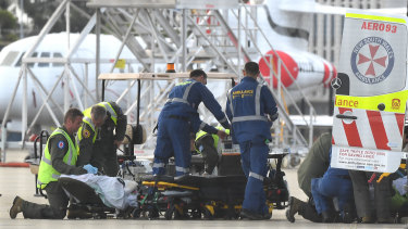 A survivor of the volcano eruption being removed on a stretcher from an RAAF Hercules at Sydney Airport on Thursday.