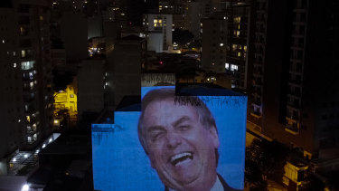 An image of Jair Bolsonaro is projected on a building's wall as residents bang pots and pans in Sao Paulo on Thursday evening.
