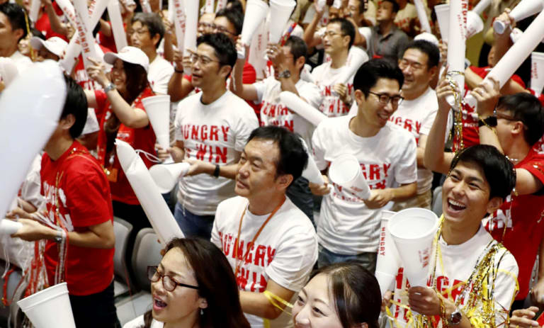 Employees of Nissin Food Products watch the live broadcast of the US Open final.