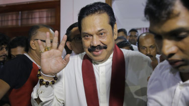 Newly appointed Sri Lankan Prime Minister Mahinda Rajapaksa, center, leaves a Buddhist temple after meeting his supporters in Colombo.