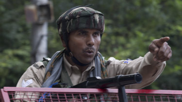 An Indian Paramilitary soldier orders a Kashmiri man to turn back near a temporary check point during curfew in Srinagar, Indian controlled Kashmir.