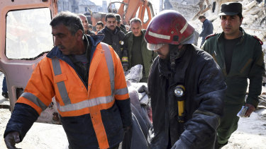 In this photo released by the Syrian official news agency SANA, rescue workers carry a victim where, according to SANA, the five-story building collapsed early on Saturday, killing 11.