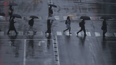 People walk on a pedestrian crossing in the rain in Tokyo. Japan is expecting its 10th typhoon this year.