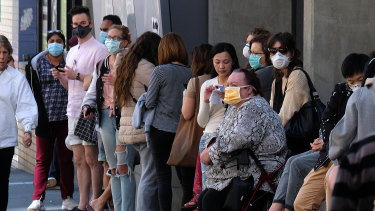 People wait outside the Royal Melbourne Hospital to be tested for coronavirus at a screening clinic on Tuesday.