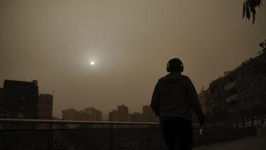 A man walks beneath a cloud of red dust in Santa Cruz de Tenerife, Spain.