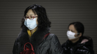 A woman wears a mask at a subway station in Wuhan, where the number of confirmed cases of the new coronavirus has jumped sharply.