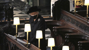 The Queen stands as Prince Philip's coffin is carried into St George's Chapel.