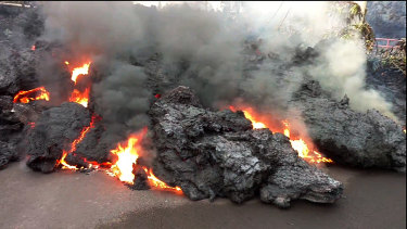 A lava flow advances down a road in the Leilani Estates subdivision near Pahoa on the island of Hawaii on Monday.