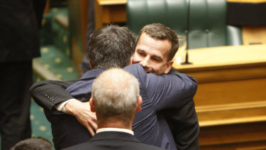 Euthanasia bill sponsor David Seymour, rear right, embraces other MPs in Parliament in Wellington, New Zealand, on November 13.