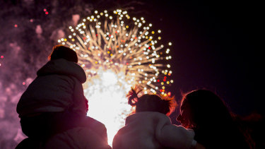 A family watches the New Year's Eve fireworks in Melbourne.