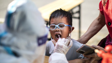 A medical worker takes samples during a mass COVID-19 test in a residential block in Wuhan, Hubei Province, China.