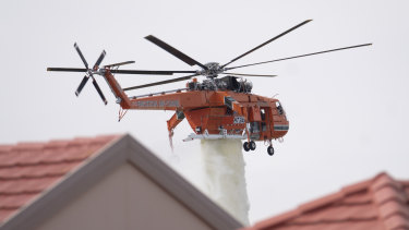 An air-crane drops water to assist firefighters as they battle a grass fire in Taylors Lakes on Monday.
