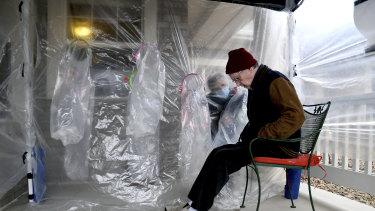 "Lynda Hartman, 75, background, visits her 77-year-old husband, Len Hartman, in a ""hug tent"" in Colorado."