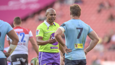 South African referee Egon Seconds speaks to Waratahs back-rower Michael Hooper.