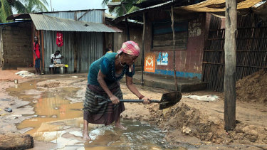 A woman tries to create a drainage system outside her shop in Pemba, Mozambique on Sunday.