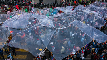 Protesters cover themselves prepare to be sprayed by water cannons in Yangon, Myanmar.