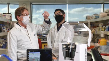Professor of pharmaceutical biology Colin Pouton and bio-engineer Dr Harry Al-Wassiti with the new  trial COVID-19 vaccine at Monash Institute of Pharmaceutical Sciences.