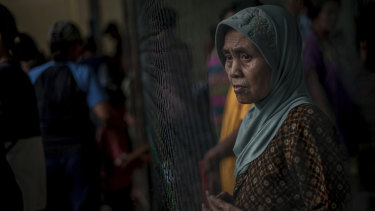 A survivor pauses at a temporary shelter for those affected by Saturday's tsunami in Carita, Indonesia.