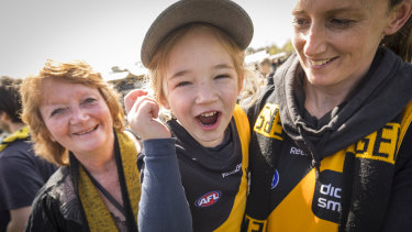 Kathy Bailey, Kellie Bailey-Lynn and Evie, lap up the atmosphere at Punt Road after Richmond's massive grand final win