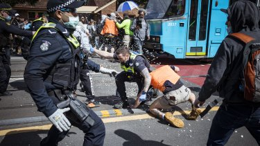 Protesters clashed with police during a violent anti-lockdown rally in Melbourne's inner east on Saturday.