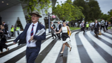 Racegoers bolt for shelter on a wet Derby Day at Flemington Racecourse.