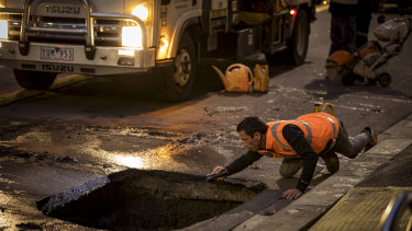 Workers investigate the sinkhole on Collins Street.