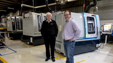 Pat Boland, co-founder and director of ANCA and Mark Patman at ANCA's factory in Bayswater with the machines manufacturing components for the ventilators.