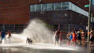 People stand in the spray of water coming from a fire hydrant in the Bronx borough of New York, US.
