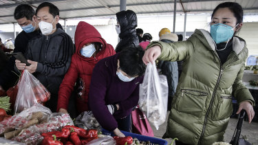 Wuhan residents wear masks to buy vegetables.