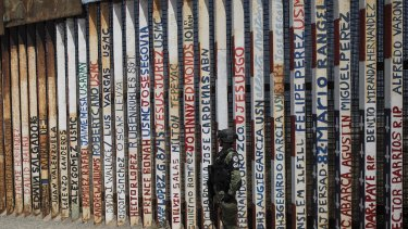 A Mexican National Guard soldier stands guard at a section of the US-Mexico border wall in Tijuana, where the names of deported US military veterans are listed.