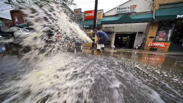 Water is pumped from the basement of a business on Noblestown road in Oakdale, Pennsylvania.