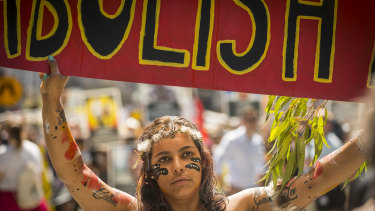 A woman carries a sign calling for the abolition of Australia Day while taking part in the Invasion Day march in Melbourne.