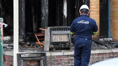 Investigators examine a heater at the scene of the fire.