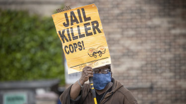 Steven Hudson protests near the site where a black man, who was taken into police custody the day before, died.