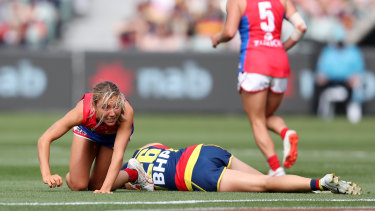 Melbourne's Eliza McNamara and the Crows' Chelsea Randall after a heavy clash.