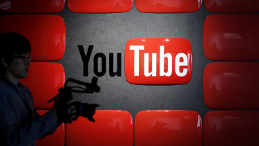 An employee holding recording equipment walks past the YouTube logo displayed at the company's studio in Tokyo, Japan.