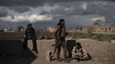 US-backed Syrian Democratic Forces (SDF) fighters stand in an area recently taken by SDF as fighting against Islamic State militants continues in the village of Baghouz, Syria, on Sunday.