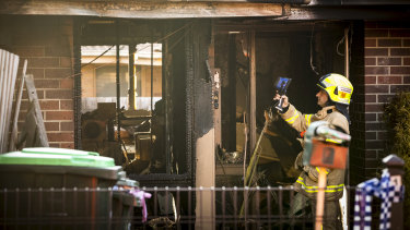 MFB firefighters check the remains of a house fire in Emma Court, Thomastown for hotspots.