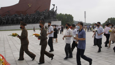 Masks are visible as people visit the Mansu Hill to pay respects to the late North Korean leaders Kim Il-sung and Kim Jong-il in Pyongyang, North Korea.