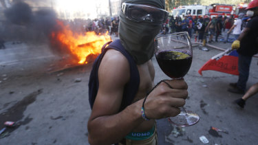 A protester poses with a glass of wine during the strike on Tuesday.