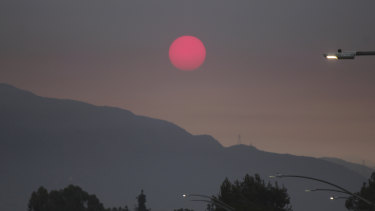 Smoke from wildfires burning east of Los Angeles dims the sunrise on seen from Pasadena, California.
