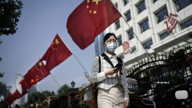 A women wears a face mask as she passes a hospital gate in Wuhan.