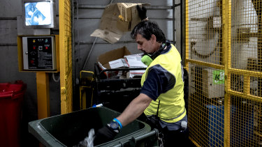 A cleaner sorts recyclable items from general waste.
