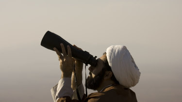 A cleric searches the sky to look for the new moon that signals the start of Eid.