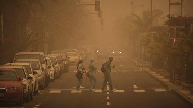 People in carnival dress walk across a street crossing in a cloud of red dust in Santa Cruz de Tenerife, Spain.