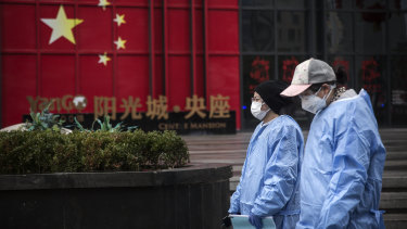 People wear protective masks and clothing  in Wuhan on Monday.