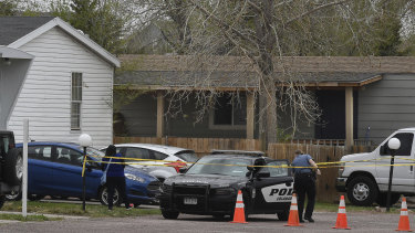 A police officer goes to help a person who was in a different mobile home get to her car in Colorado Springs, Colorado.