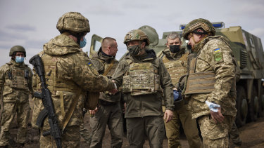 Ukrainian President Volodymyr Zelenskiy shakes hands with a soldier as he visits the war-hit Donbas region, in eastern Ukraine.