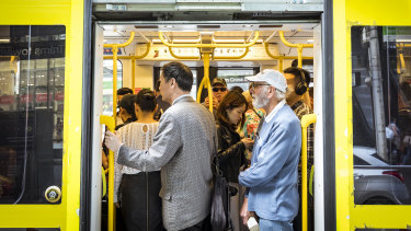 Commuters pack into a crowded tram along Bourke Street during the lunchtime break earlier this month.